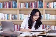 Estudiante precioso que hace la asignación de escuela en biblioteca Imagen de archivo