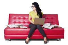 Estudiante precioso que se sienta en el sofá mientras que estudia Fotografía de archivo
