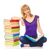 Estudiante precioso que se sienta en un piso con la pila de libros, aislada Fotografía de archivo libre de regalías