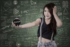 Estudiante preocupante con la bomba del examen Fotografía de archivo libre de regalías