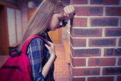 Estudiante preocupante que se inclina contra la pared Foto de archivo