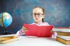 Estudiante primario caucásico bonito Girl Read Book imágenes de archivo libres de regalías