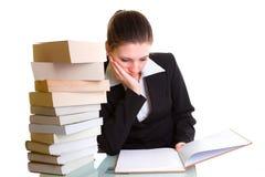Estudiante que aprende con la pila de libros en el escritorio Foto de archivo libre de regalías