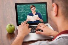 Estudiante que asiste a la conferencia de la matemáticas en línea en el ordenador portátil Imagenes de archivo