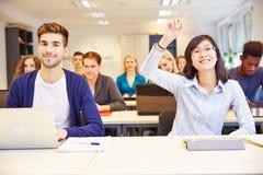 Estudiante que aumenta la mano en universidad Imagenes de archivo