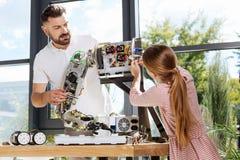 Estudiante que ayuda a su profesor con el robot a armar la construcción Imagenes de archivo