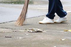 Estudiante que barre las hojas secadas en el piso en escuela fotos de archivo libres de regalías