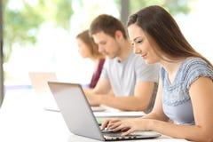 Estudiante que busca en línea en una sala de clase Imagenes de archivo