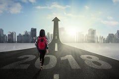 Estudiante que camina en el camino con la flecha ascendente Imagen de archivo