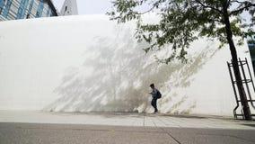Estudiante que camina en universidad moderna del campus interno metrajes