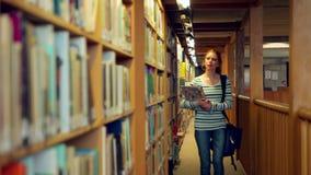Estudiante que camina a través de la biblioteca metrajes
