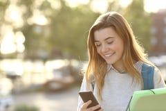 Estudiante que camina y que usa el teléfono elegante Imagen de archivo libre de regalías
