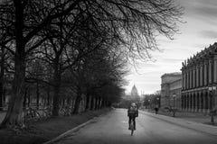 Estudiante que completa un ciclo en el camino por la tarde el día de invierno Imagenes de archivo