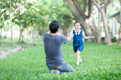 Estudiante que corre en el father& x27; manos de s a abrazar Foto de archivo