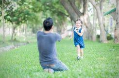 Estudiante que corre en el father& x27; manos de s a abrazar Imagen de archivo