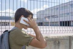 Estudiante que descansa fuera de una escuela y que juega con un teléfono móvil Imagenes de archivo
