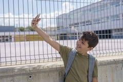 Estudiante que descansa fuera de una escuela y que juega con un teléfono móvil Fotos de archivo