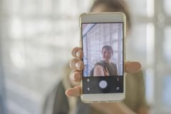 Estudiante que descansa sobre la escuela y que juega con un teléfono móvil Fotografía de archivo libre de regalías
