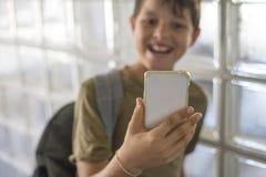 Estudiante que descansa sobre la escuela y que juega con un teléfono móvil Fotos de archivo libres de regalías