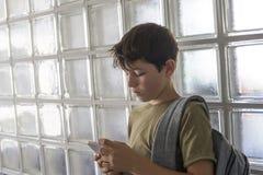 Estudiante que descansa sobre la escuela y que juega con un teléfono móvil Imágenes de archivo libres de regalías