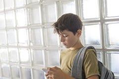 Estudiante que descansa sobre la escuela y que juega con un teléfono móvil Imagenes de archivo