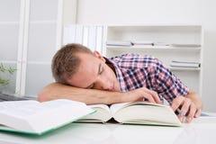 Estudiante que duerme en el escritorio Imagenes de archivo