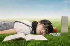 Estudiante que duerme en el ordenador portátil en la hierba Imágenes de archivo libres de regalías