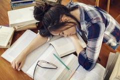 Estudiante que duerme en los libros de papel imagen de archivo libre de regalías