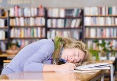 Estudiante que duerme en una biblioteca de universidad Fotografía de archivo