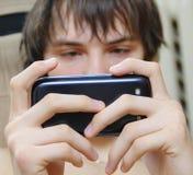Estudiante que envía el mensaje de texto Fotos de archivo