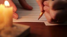 Estudiante que escribe una música: músico que compone con un lápiz en un libro de música con luz de una vela mano del primer del  almacen de video