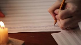 Estudiante que escribe una música: músico que compone con un lápiz en un libro de música con luz de una vela mano del primer del  almacen de metraje de vídeo