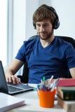 Estudiante que escucha la música Imagen de archivo libre de regalías