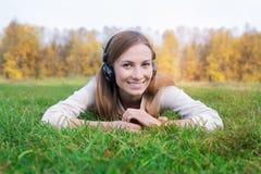 Estudiante que escucha los auriculares y que miente en hierba verde Fotografía de archivo libre de regalías