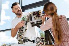 Estudiante que está a punto de tapar los alambres en la pieza del robot Foto de archivo libre de regalías