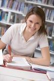 Estudiante que estudia en biblioteca Imagen de archivo