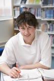 Estudiante que estudia en biblioteca Foto de archivo libre de regalías