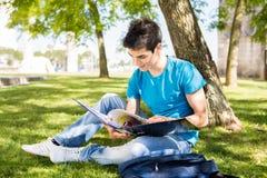 Estudiante que estudia en el jardín de la escuela Foto de archivo