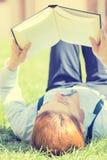 Estudiante que estudia en el parque que lee un libro foto de archivo