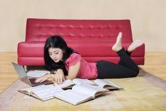 Estudiante que estudia en la alfombra en casa Fotografía de archivo libre de regalías