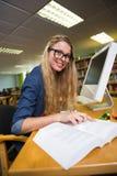 Estudiante que estudia en la biblioteca con el ordenador Fotos de archivo