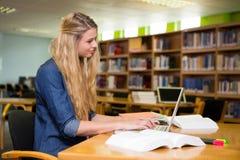Estudiante que estudia en la biblioteca con el ordenador portátil Foto de archivo libre de regalías