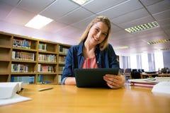 Estudiante que estudia en la biblioteca con la tableta Foto de archivo