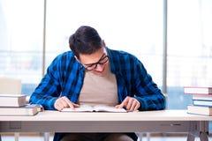 Estudiante que estudia en la biblioteca vacía con el libro que se prepara para ex Foto de archivo libre de regalías