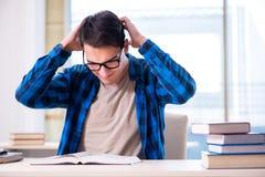 Estudiante que estudia en la biblioteca vacía con el libro que se prepara para ex Imagen de archivo libre de regalías