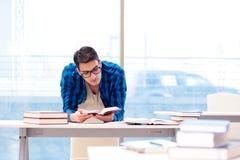 Estudiante que estudia en la biblioteca vacía con el libro que se prepara para ex Fotos de archivo libres de regalías
