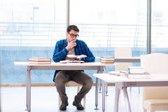 Estudiante que estudia en la biblioteca vacía con el libro que se prepara para ex Imágenes de archivo libres de regalías
