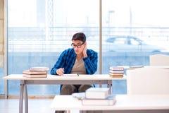 Estudiante que estudia en la biblioteca vacía con el libro que se prepara para ex Imagen de archivo
