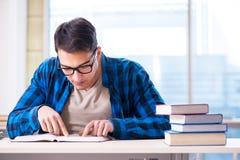Estudiante que estudia en la biblioteca vacía con el libro que se prepara para ex Fotos de archivo