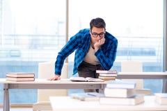 Estudiante que estudia en la biblioteca vacía con el libro que se prepara para ex Imagenes de archivo